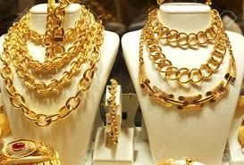 a lot of gold chains necklaces and bracelets in the window of the jewelry