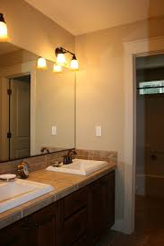 bathroom beige bathroom design idea feat awesome frameless mirror and eclectic twin wall mounted lights