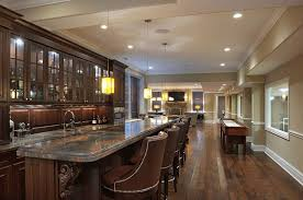 luxury home lighting. luxury home bar with dark cabinetry and long granite counter lighting