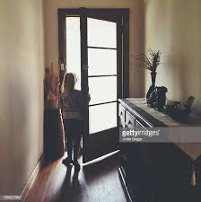 open front door. Child Standing At Open Front Door Of House