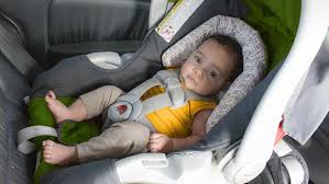 baby with no socks on sitting in a car seat