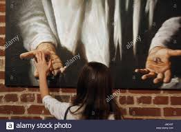 young girl touching the hand of christ in painting
