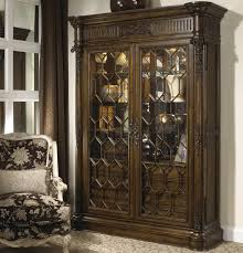 antique hardwood cabinet with large glass door and hand carved leaf brass plus striped accent on ivory carpet