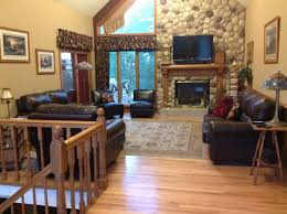 upstairs living room with leather furniture fireplace and large