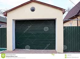 garage with closed green gates and part of the fence in the street near the road