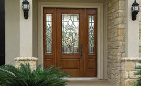 stylish brown wooden front entry door with stained glass accents plus black handles and cream wall