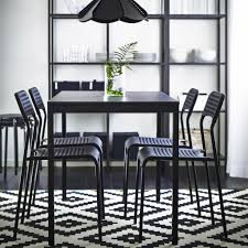 A Black Dining Table With Chairs And A Blackbrown Storage Combination