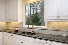 square grey stone tile backsplash with black accent cream wall painting white kitchen cabinet black granite