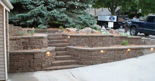 natural green trees and plants beside stone retaining wall ideas and stone stairs near garage space