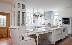 a cook s kitchen features an island fitted with a microwave topped with white marble placed directly next to a marble top island dining table lined with a