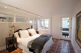 Small Bedroom Illuminated With Track Lighting Fixtures Over The Bed