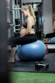 pregnant woman sitting on exercise ball in gym