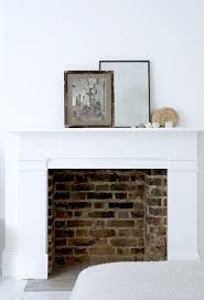 white mantel with brick fireplace