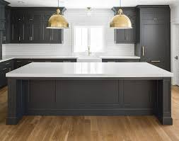 black kitchen cabinets. black kitchen cabinets with white quartz countertop, oak hardwood floor, brass accents and c