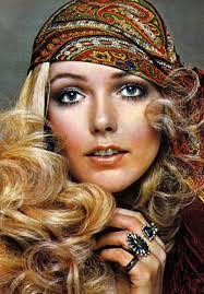 this woman in the is wearing an updated hippie look from the the way the headscarf is worn is in a hippie style the makeup and hair make it more modern