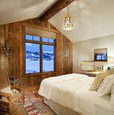 spacious and serene rustic bedroom with reclaimed wood accent wall that frames the view outside