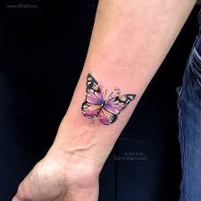 фото небольшой женской цветной татуировки на руке бабочка в стиле