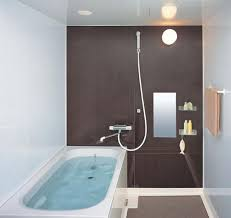 Compact Small Bathroom Layout With Brown Wall Decor Wall Lamp Square Tub  And Hanging Towel Image