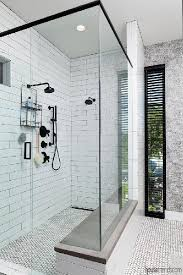 the master bathroom shower features oversized white porcelain subway tile and black matte plumbing fixtures