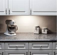 a kitchen countertop glows with under cabinet lighting
