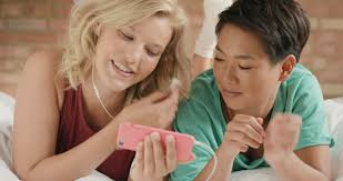 girl friends at home listening to sharing smart phone technology in pajamas happy smiling having