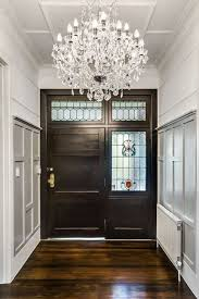 a narrow foyer featuring stained glass and an enormous crystal chandelier while the foyer itself is small it serves the purpose of preserving the privacy