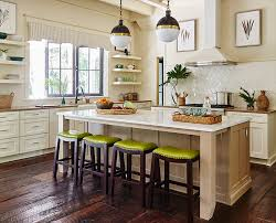 the spacious kitchen features a pair of hicks large pendants by thomas o brien over an 8 foot wide sand colored island harper brought the outdoors in with