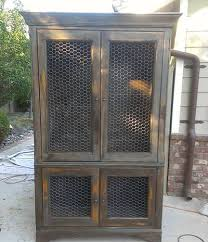 A distressed chicken wire cabinet is standing in courtyard.