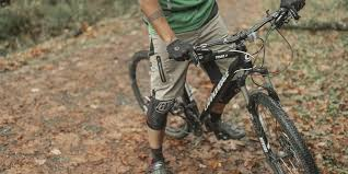 a rider stands over his mountain bike