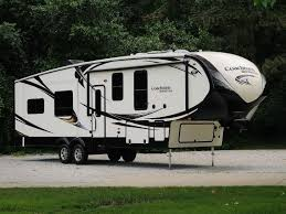 parked 2019 coachmen brookstone fifth wheel on lot next to trees at john s rv