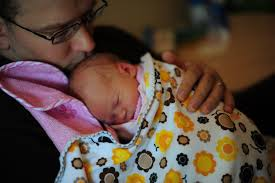 father  father holding daughter in swaddling clothes