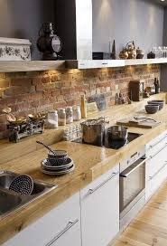 kitchen remodel with great mixture of textures from a brick backsplash to white cabinets to a light wood countertop