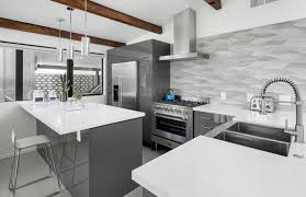 Contemporary kitchen with gray cabinets, white countertops, metallic  backsplash and exposed wood beams