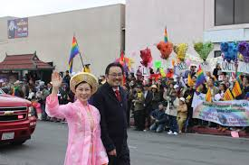 garden grove councilwoman dina nguyen acpanied by her husband joseph dovinh waves to the