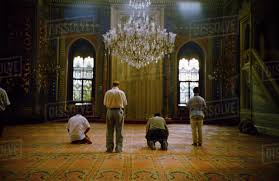 mosque interior men praying some kneeling some standing huge crystal chandelier ornate carpets arched windows istanbul turkey