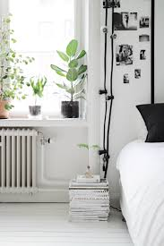 skandinavian bedroom w/ magazine stack instead of bedside table, plants,  photos