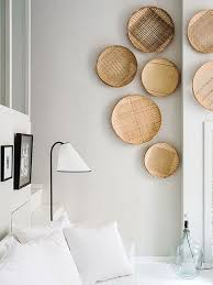 a cri white bedroom is softened and warmed up with wall baskets