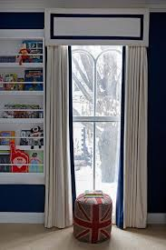 navy boy s bedroom features navy paint on wall lined with a white bookshelf next to a window dressed in an ivory cornice box and ivory curtains accented