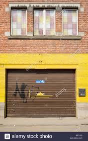 brown garage door in brick wall with yellow paint Stock Photo ...