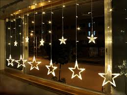 gorgeous christmas window decoration design featuring lighted hanging star  christmas ornaments on window with gold plated
