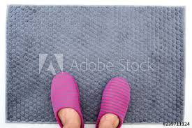 a man feet ware pink and gray strip color slippers on gray bathroom rug top view