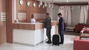 long shot of auburn haired man checking in at the reception desk another man