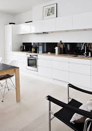white kitchen cabinets with timber bench. Black colour-back splash ...