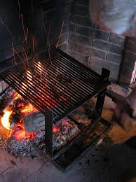 cooking at home over a wood fire adjusting logs in the fireplace to maintain the fire