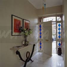 stained glass panels either side of open door in hall with pictures above modern console table