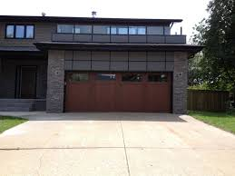 A stained steel garage door adds warmth to this contemporary home. Model  shown: Clopay