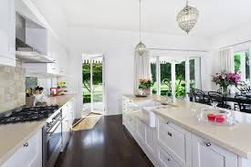 kitchen with white shaker style cabinets white quartz counter and dark hardwood floors