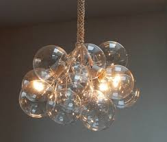 the chandelier is made from 12 hand blown glass and three clear globe bulbs held together by cables wrapped in cotton twine