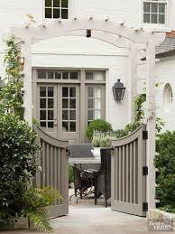 curved double garden gate with arbor and hedge painted white brick house
