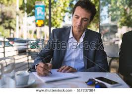 concentrate middle age businessman portrait writing stock photo  concentrate middle age businessman portrait writing an essay outdoors in rome